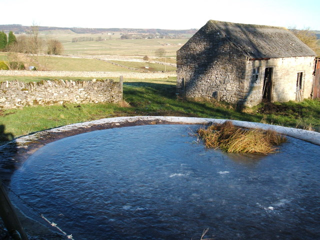 Frozen solid; dewpond at Wardlow, with barn