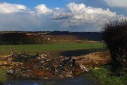 Log barrier and remains of burnt out car on Peafield Lane