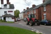 Tractor passing the Golden Lion Inn, Tipton St John