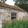 Outbuilding by a nettle-strewn footpath